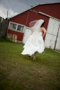 Bride running towards barn. Photo by Ralph Heinze Photography