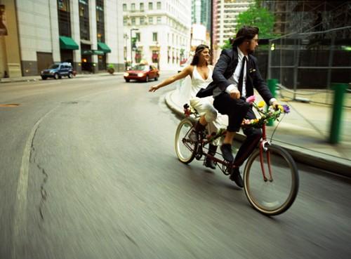 Cặp đôi trong trang phục cưới phóng dọc theo một con đường trong thành phố trên chiếc xe đạp đôi.
