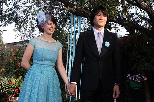 couple holding hands beneath ribbon tree