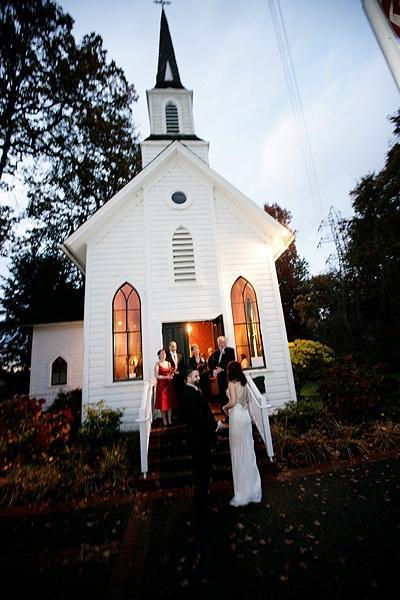 bride and groom in front of oaks pioneer church