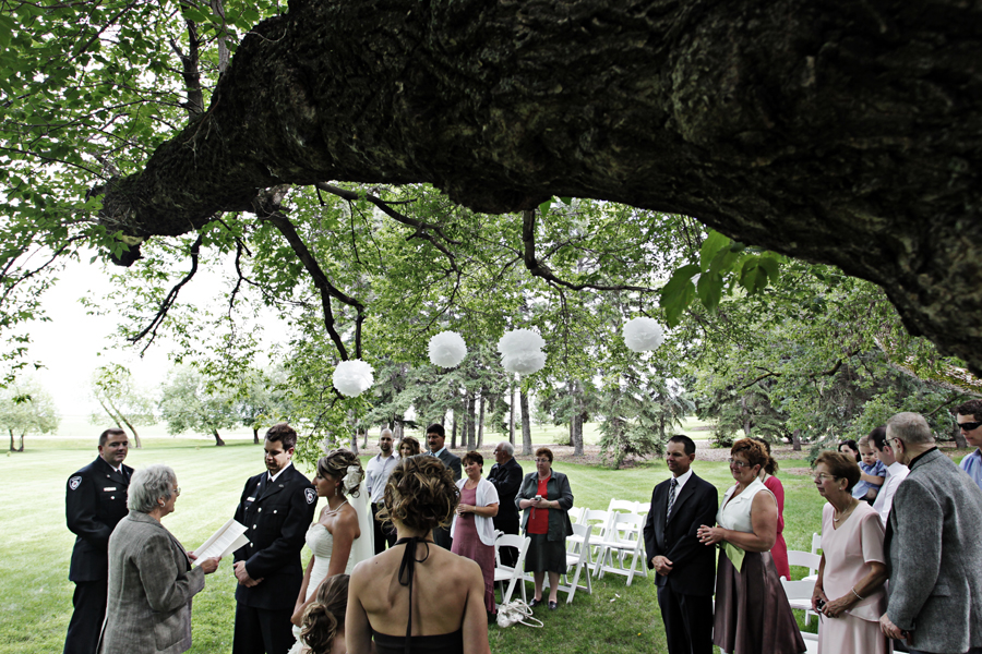 bride and groom exchanging vows under tree