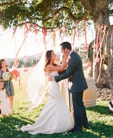 Một cây xanh với những dải ruy băng màu sắc bắt mắt là phông nền tuyệt đẹp cho đám cưới.