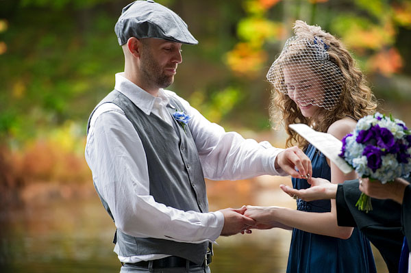 bride and groom exchanging rings in the woods