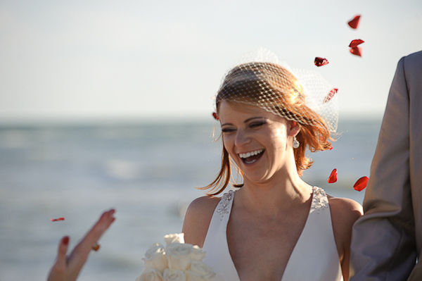 red rose petals being tossed at bride and groom