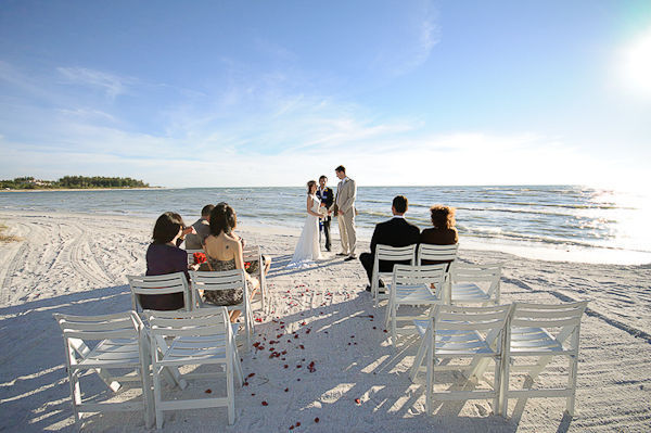 bride and groom saying their vows on the beach