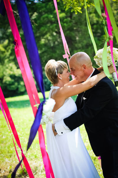bride and groom embracing under pink and purple ribbins