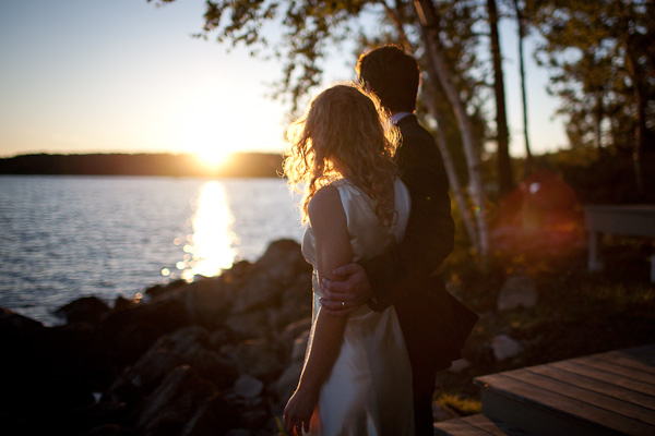 bride and groom overlooking lake at sunset