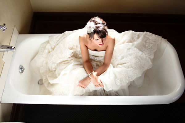 bride sitting in the bathtub in her dress