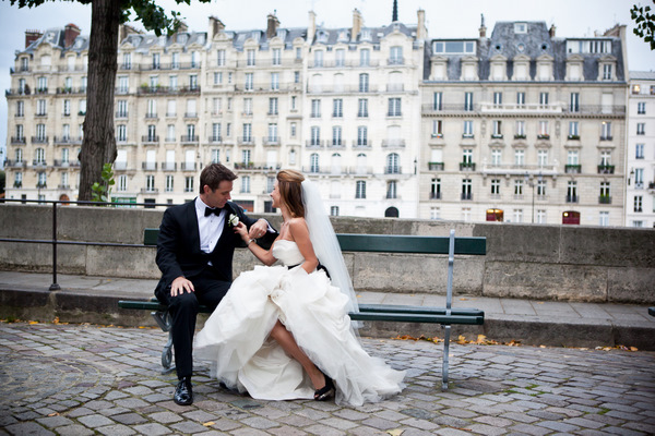 bride and groom sitting on a bench in Paris