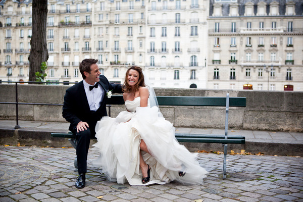 bride and groom laughing on a park bench in Paris