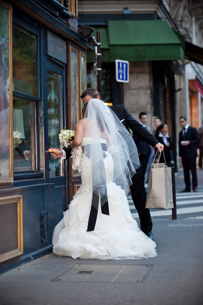 bride and groom looking in Paris shop window