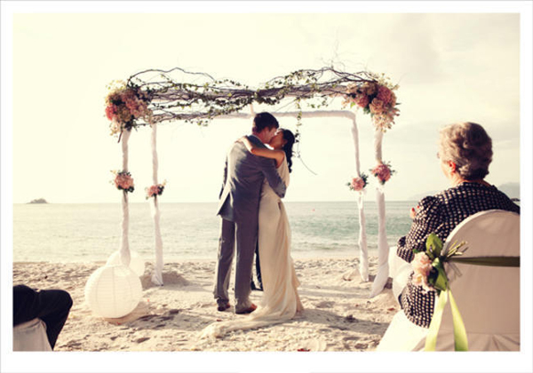 bride and groom first kiss on the beach