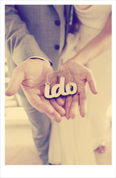 bride and groom holding i do pendant