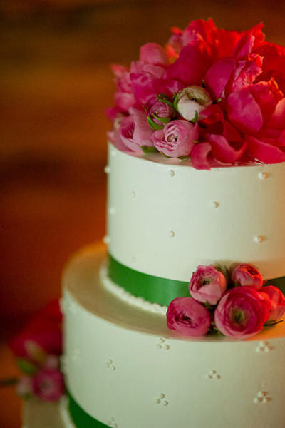 wedding cake with green ribbon and pink flowers