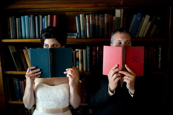 bride and groom hiding behind books