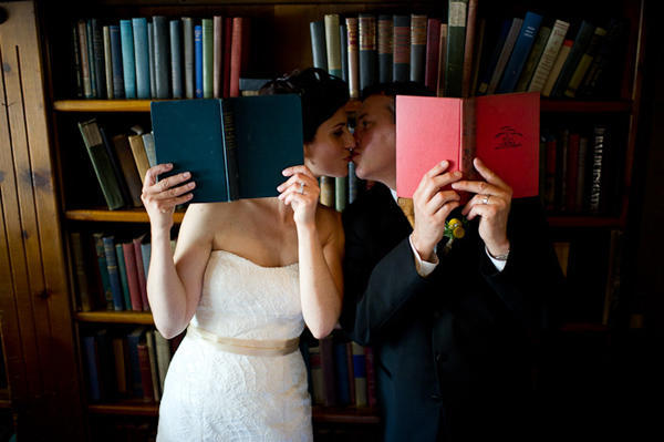 bride and groom kissing with books