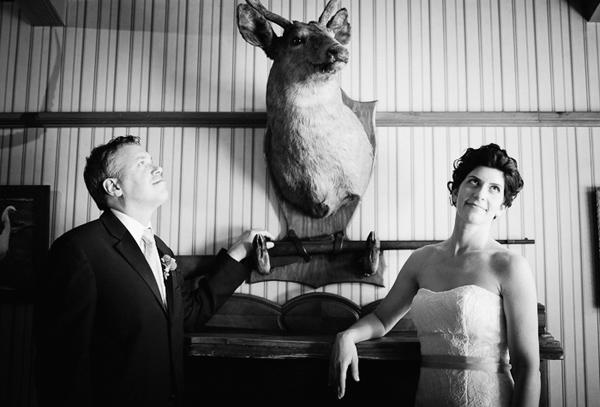 bride and groom lodge portrait with deer head