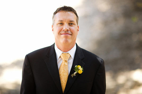 groom with yellow tie and billy button boutonniere