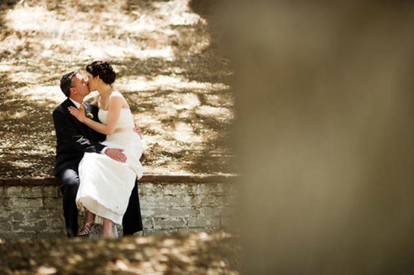 bride and groom kissing on brick wall