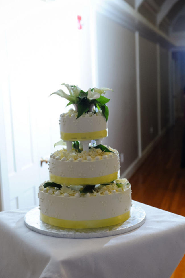 yellow and white wedding cake with calla lily cake topper