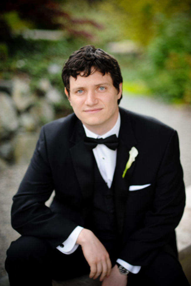 groom in black tuxedo with lily boutonniere