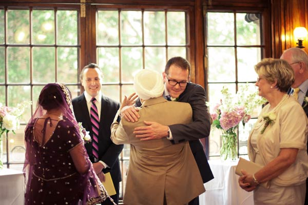 groom hugging father of the bride at the altar