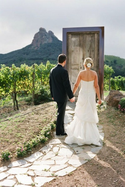 These vintage doors are set up so that the couple can walk through them. I like the unexpected use of them outside as well as the symbolism they provoke. & Vintage Door Wedding Decor