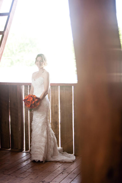 bride posing in barn with orange bouquet