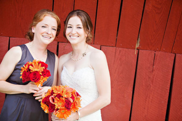bride and maid of honor with orange and red bouquets