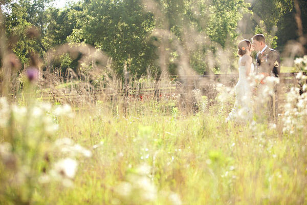 bride and groom kissing in farm field