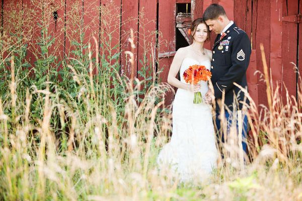 bride and groom portrait outside red barn