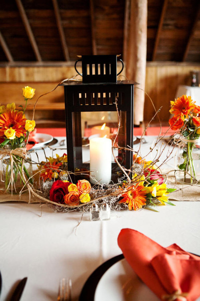 rustic lantern with orange and red rose centerpiece