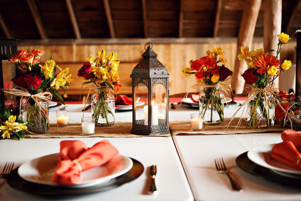 barn wedding table setting with lantern and yellow and orange centerpieces