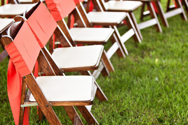 wooden folding chairs with orange ribbons