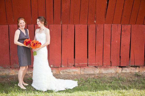 bride and groom posing against red barn
