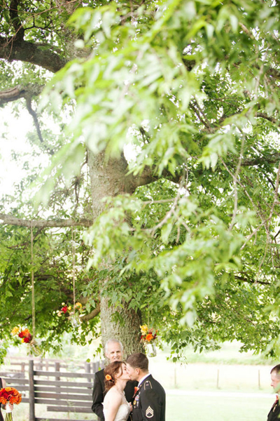 bride and groom kiss under tree