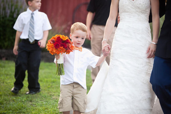 couple's son carrying wedding bouquet