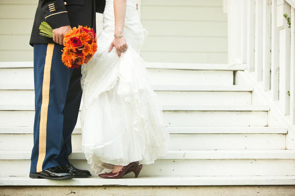 military groom holding bride's bouquet