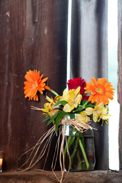 orange and red flower arrangement in mason jar