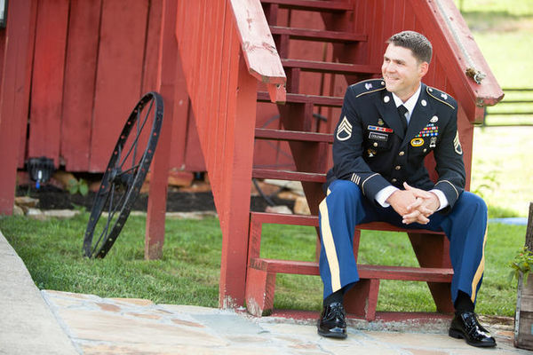 groom in military uniform outside barn