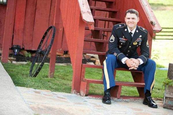 groom sitting on barn stairs