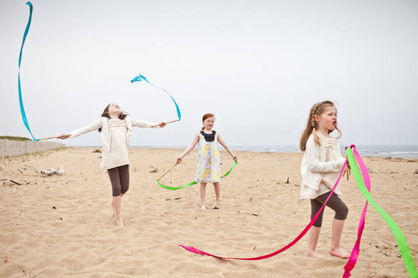 young wedding guests on the beach with ribbon wands