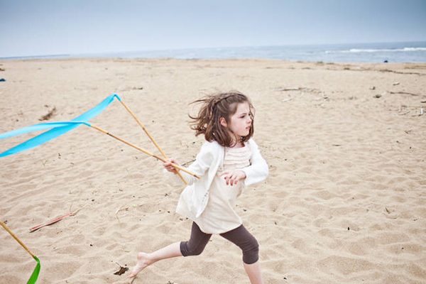flower girl running down the beach with ribbon wands