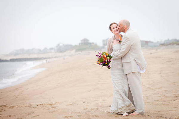 groom kissing bride on the beach