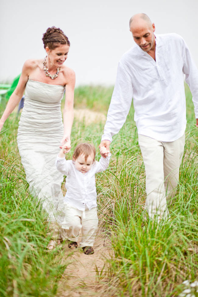 bride and groom walking with toddler on the beach