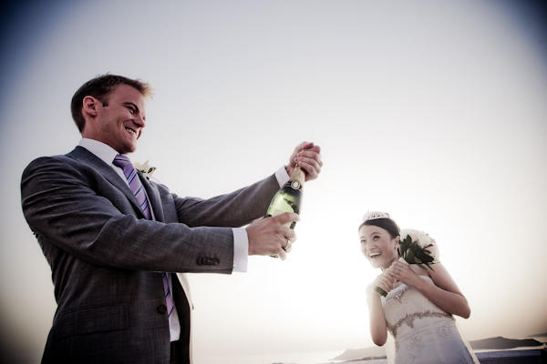 groom popping a bottle of champagne