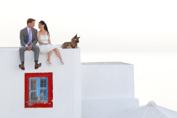 bride and groom sitting on Santorini rooftop