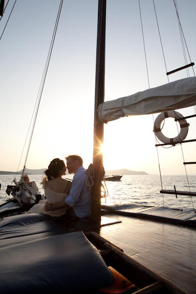 bride and groom on a sailboat at sunset
