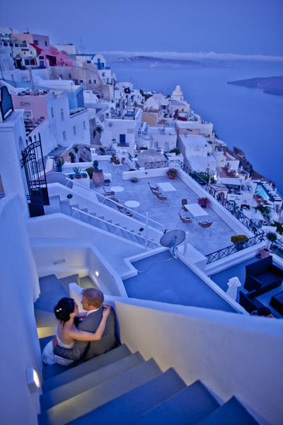 bride and groom sitting on steps in Santorini