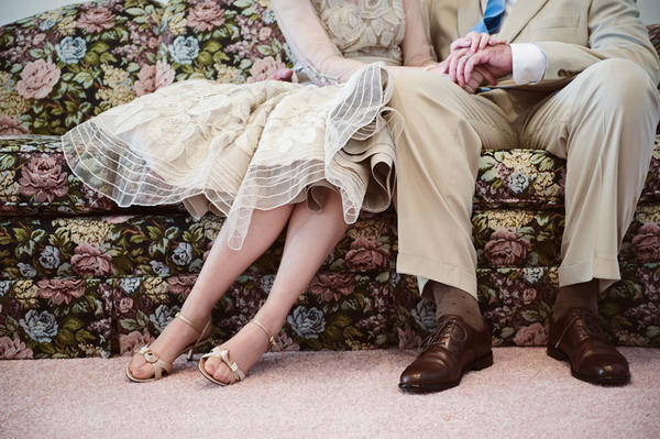 bride and groom sitting on floral couch